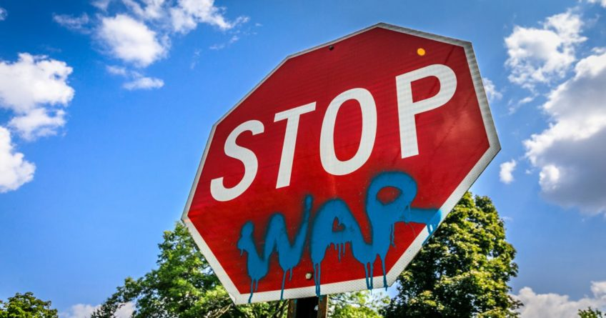 Stop sign War spray painted on